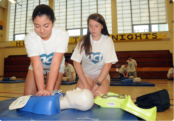 two students practice life saving skills on a test dummy