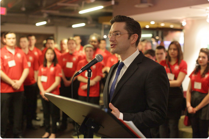 MP Pierre Poilievre speaks in front of a crowd of Skills volunteers