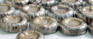 Six silver, small and round Electrolytic melt rounds sit on a white surface