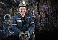 A smiling miner in a dimly lit mine
