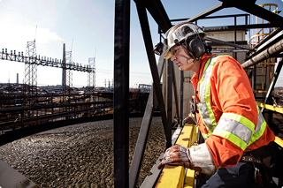 A Vale employee outdoors, in full safety gear, wearing a hard-hat and protective earphones