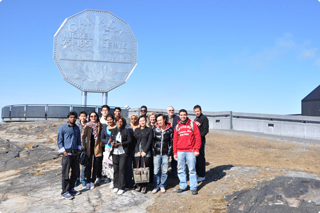 A group of recent graduates in front of the Sudbury nickel