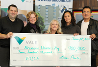 A group of Vale employees present a large, novelty cheque to community members
