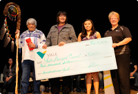 Vale employees handing out a novelty cheque at a community event