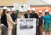 A group of Vale employees wearing hard hats presenting a new project to the community