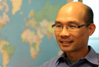 A smiling Vale employee wearing glasses, standing in front of a world map
