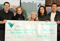Vale employees present a large, novelty cheque to employees at Brandon University